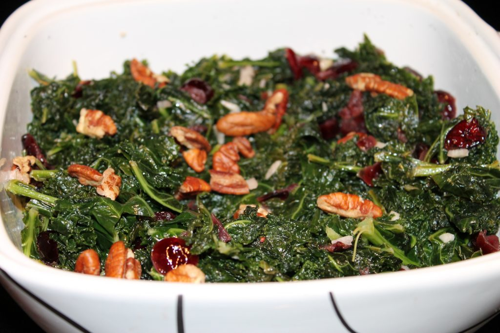 Cooked kale with pecans and cranberries in square casserole dish.