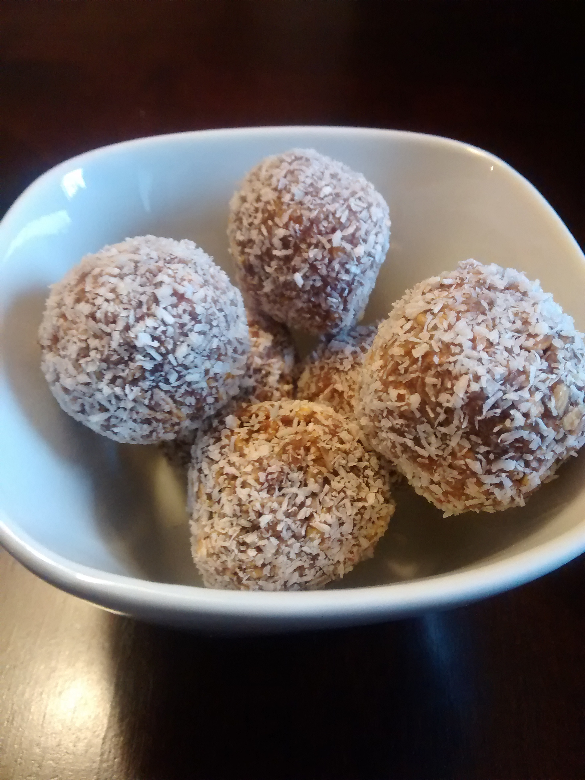 Snowball Cookies rolled in flaked coconut and piled in a white ceramic bowl