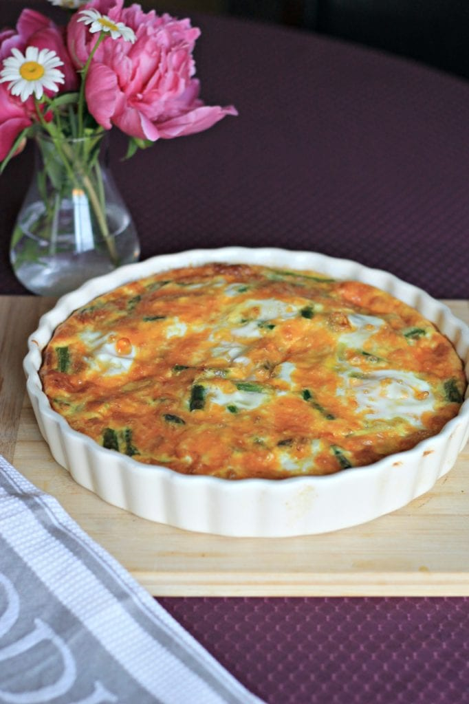 Finished quiche in cream quiche dish on wooden cutting board