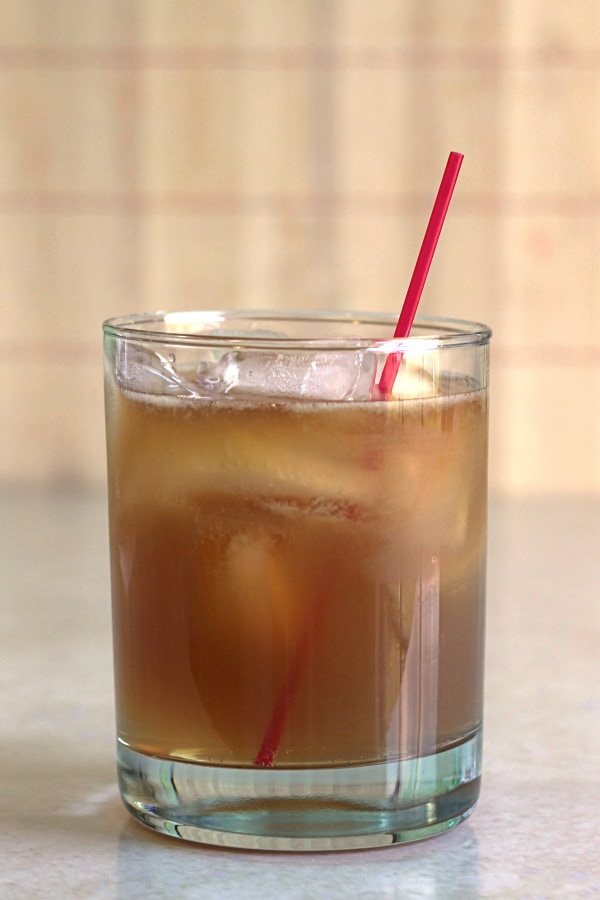 Bourbon cocktail in clear tumbler with red straw