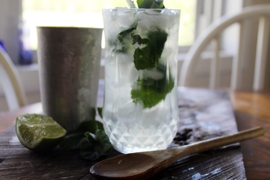 Fresh mojito in crystal glass on a cutting board with fresh mint and fresh lime