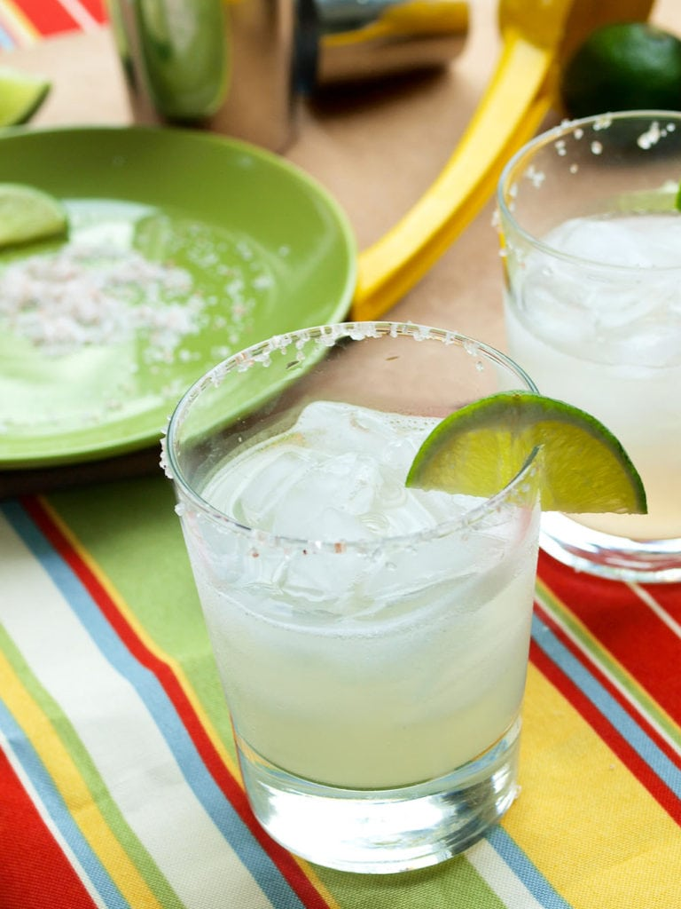 Glasses filled with the best margarita dipped in salt and served with fresh lime