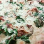 Finished pizza with bubbling cheese and spinach