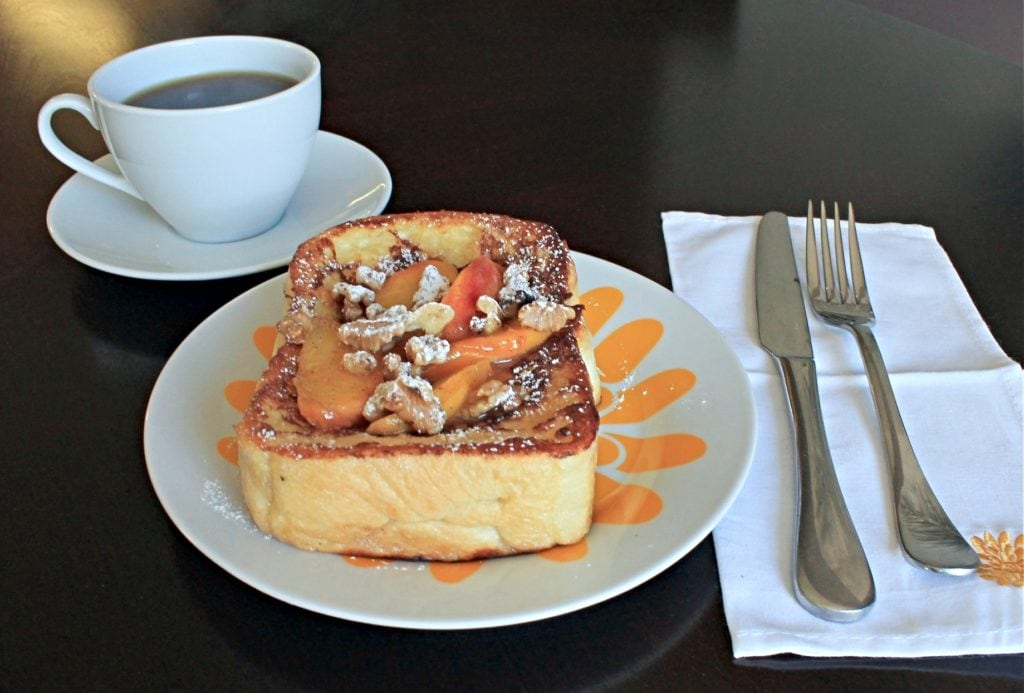 Stuffed French Toast with fresh peaches on a floral plate with cup of coffee