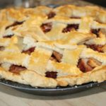 Freshly baked apple pie on wooden cutting board