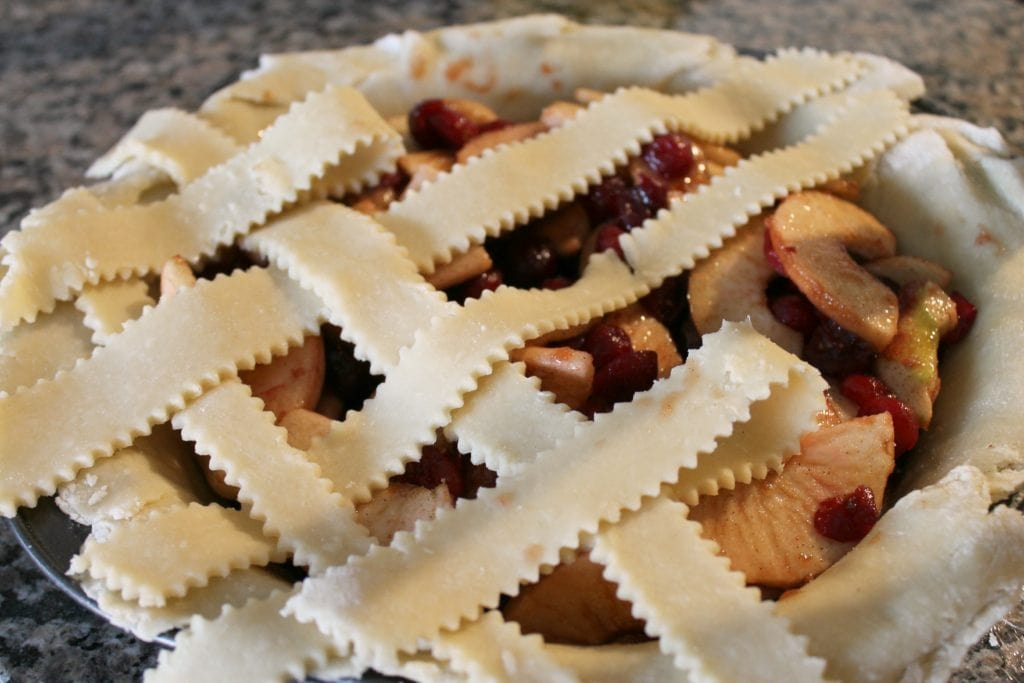 Uncooked cranberry apple pie with lattice top on counter top