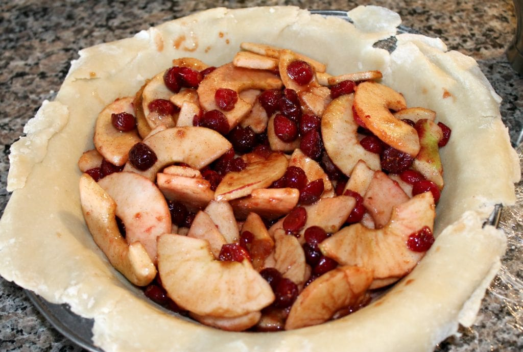 Open pie crust with chopped apples and cranberries