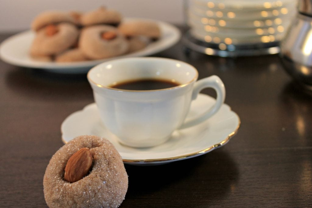 Amaretti cookie leaning on espresso cup and saucer with plate of cookies in the back