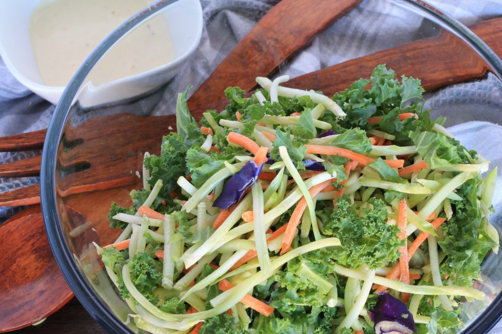 Kale Salad in glass bowl with wooden serving utensils