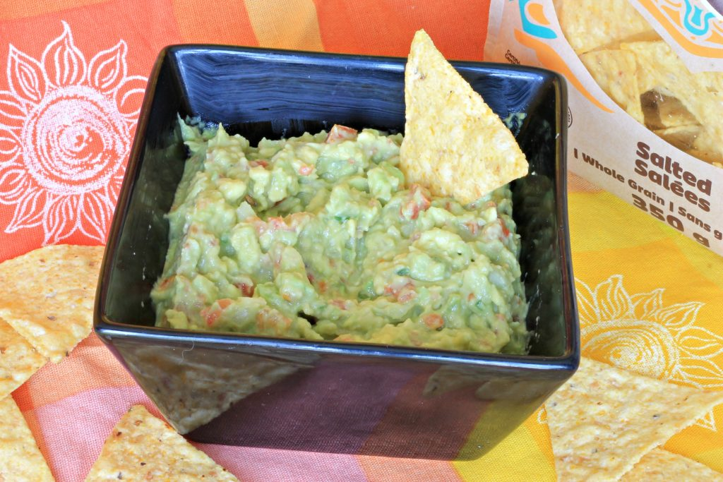 Black square bowl full of fresh guacamole with tortilla corn chip
