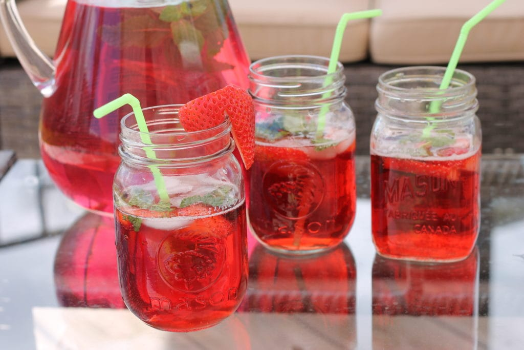 Strawberry Mint Cocktail Drink in clear glass pitcher on patio table with mason jar glasses