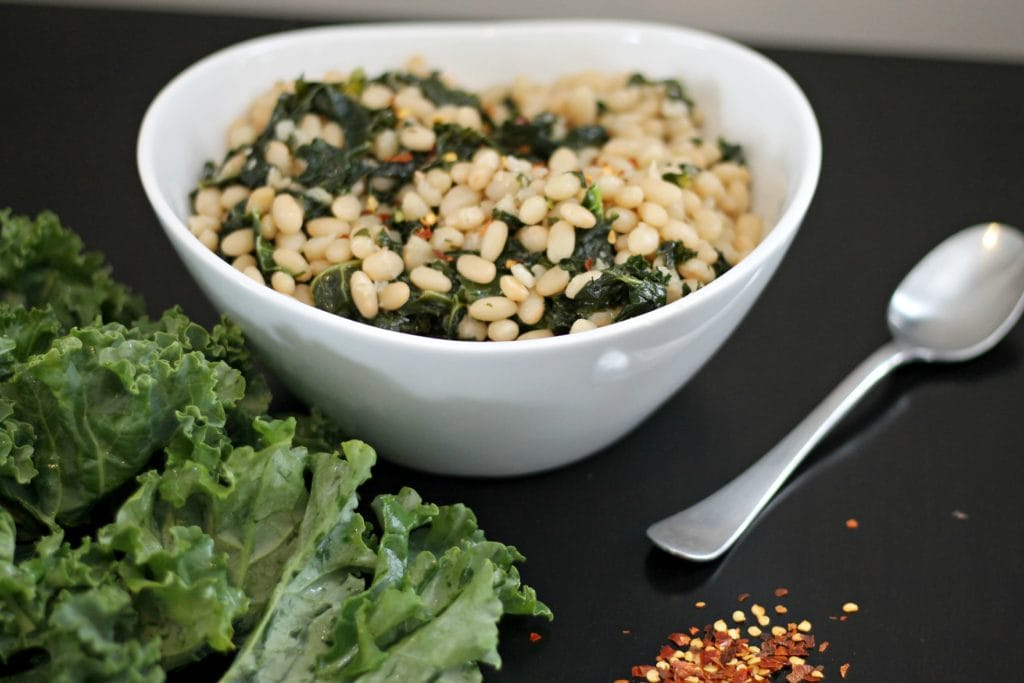 White Bean and Kale Salad in white ceramic bowl on black tablecloth.