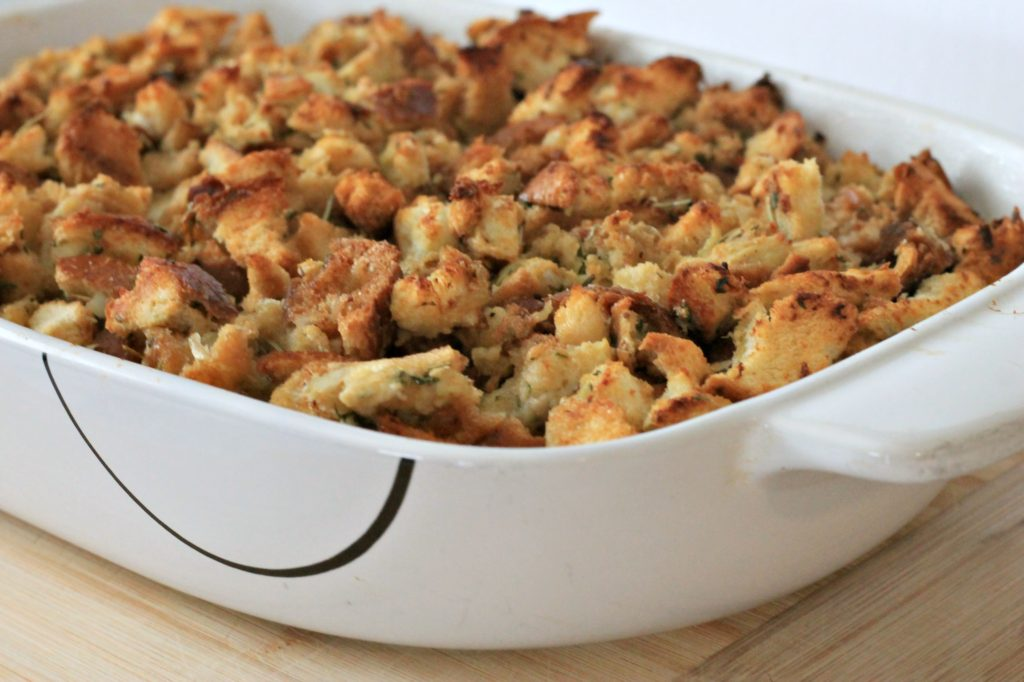 Cooked Stuffing in white casserole dish on wooden cutting board