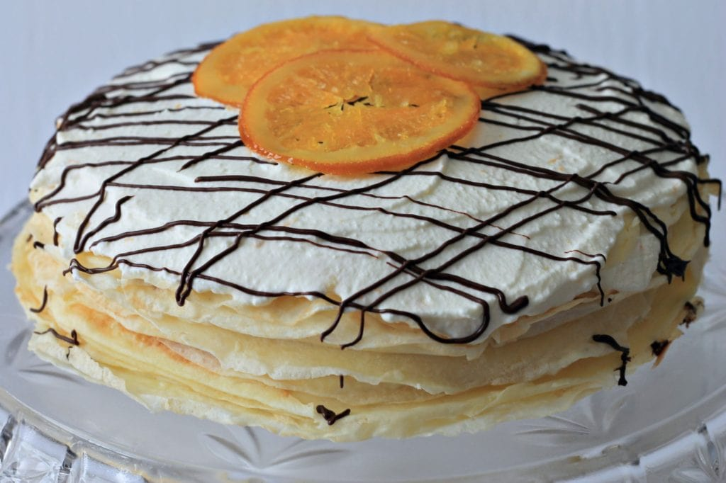 Assembled Crepe Cake with candied oranges on top - sitting on glass cake stand