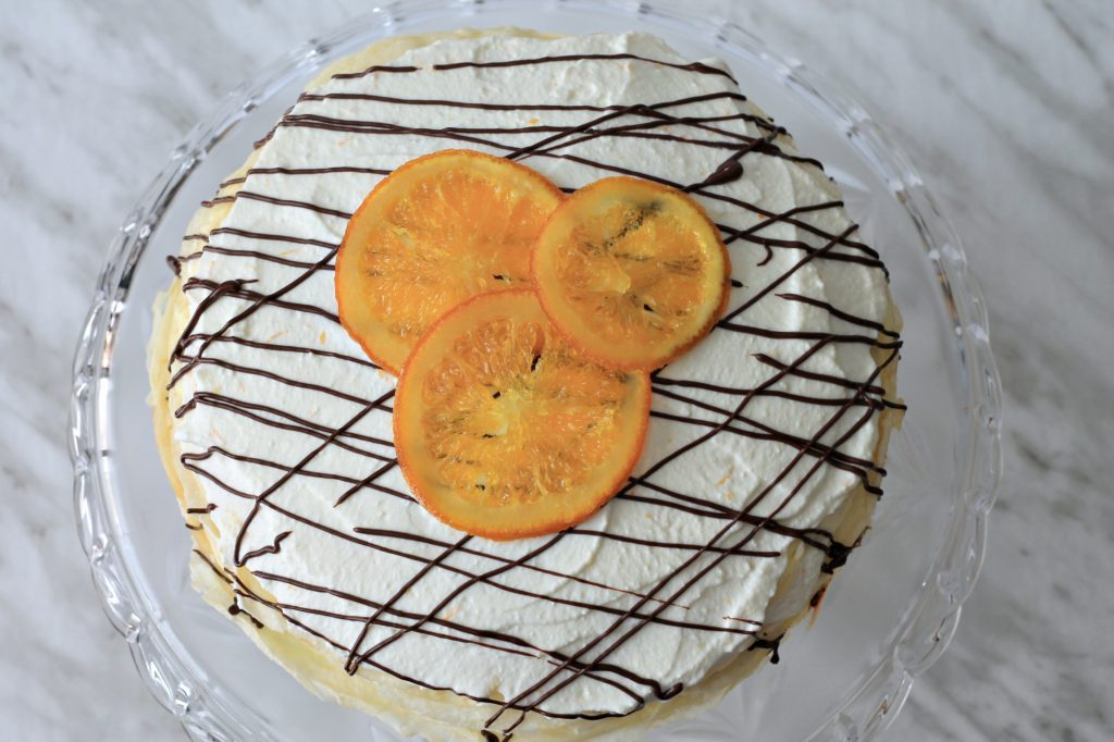 Finished crepe cake with drizzled chocolate and candied oranges