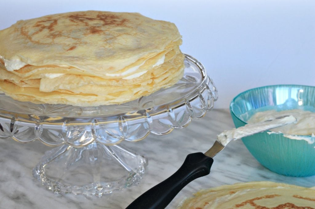 Multiple crepes stacked with cream filling on glass cake stand