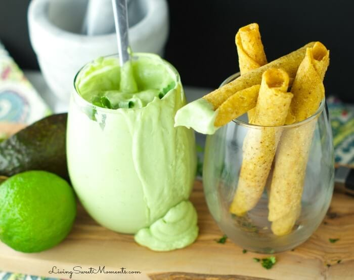 Glass of creamy avocado dip with rolled corn chips