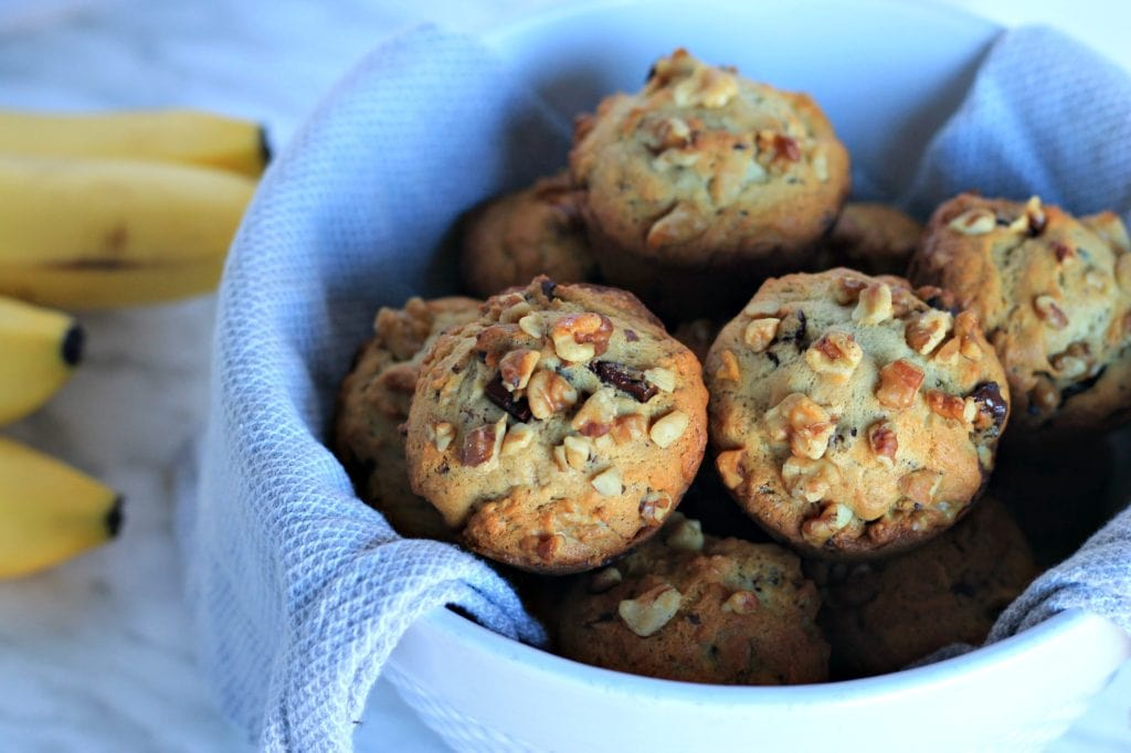 Banana Bread muffins in white bowl with bunch of bananas