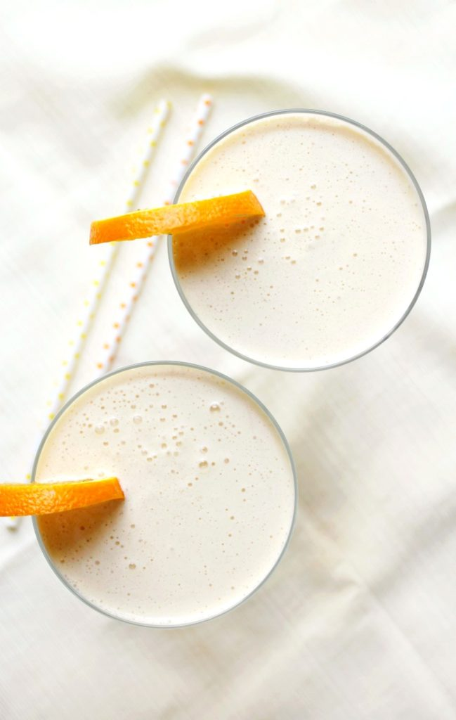 Two glasses of Orange Julius Cocktails with orange slices on top