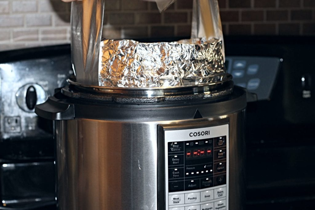Foil Lift being used to gently lower pan into pressure cooker. Note we also wrapped the side of our pan to prevent spillage but this is not neccessary.