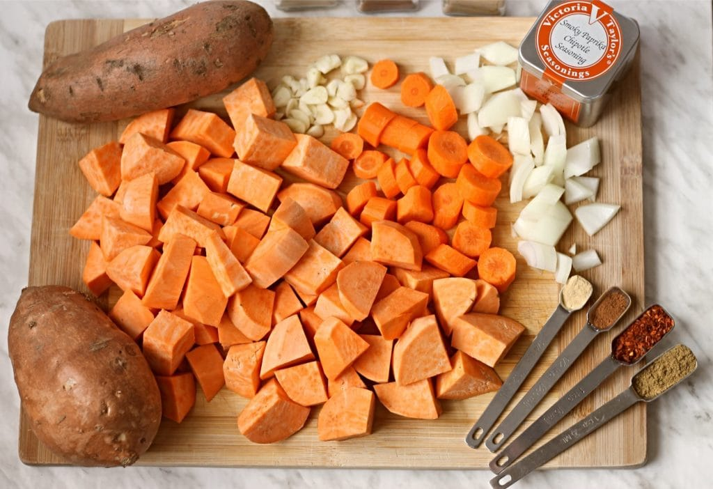 Wooden cutting board with diced sweet potatoes, carrots, onions and other ingredients to make sweet potato soup.