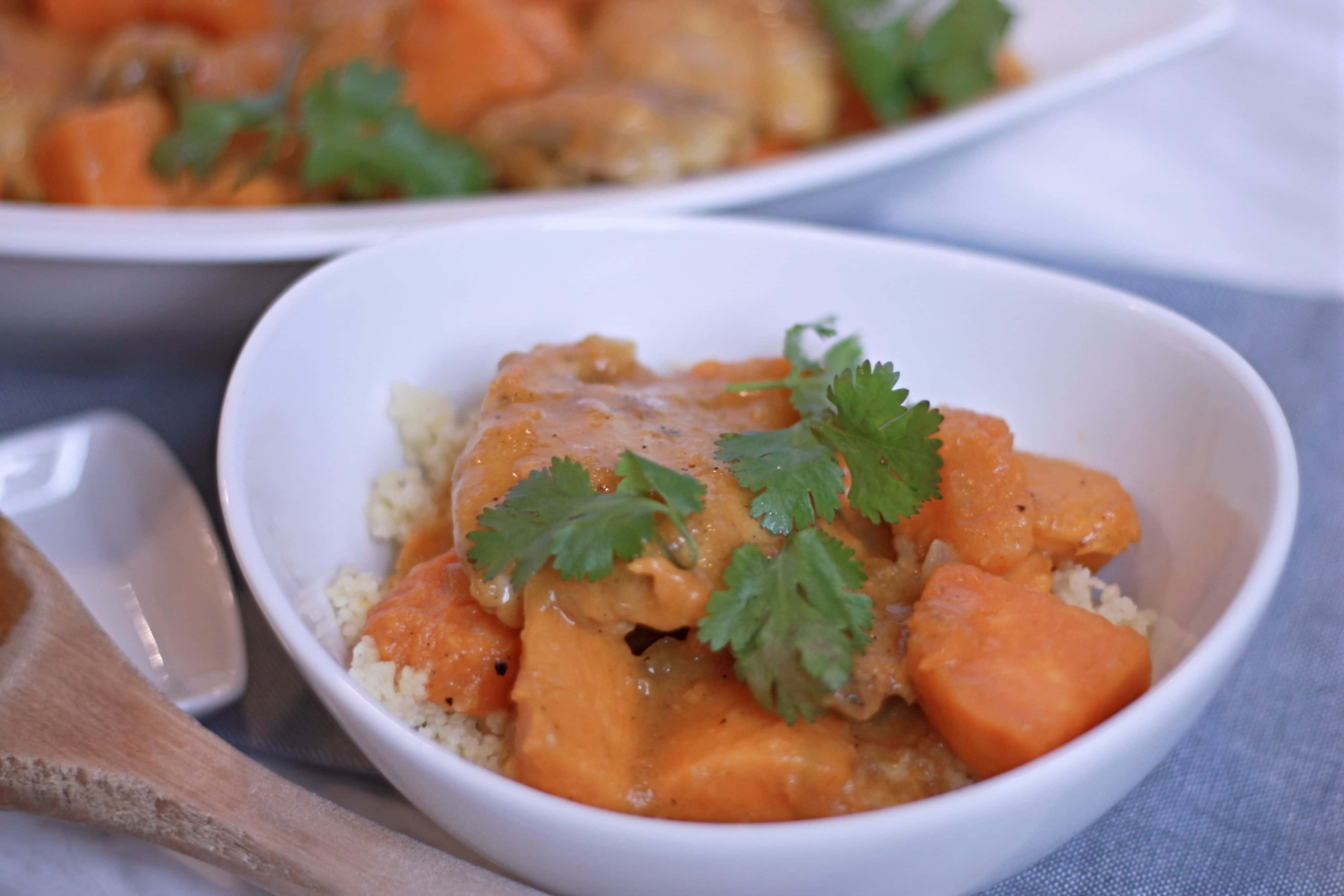 White serving bowl full of Moroccan Chicken Stew with wooden spoon and fresh cilantro