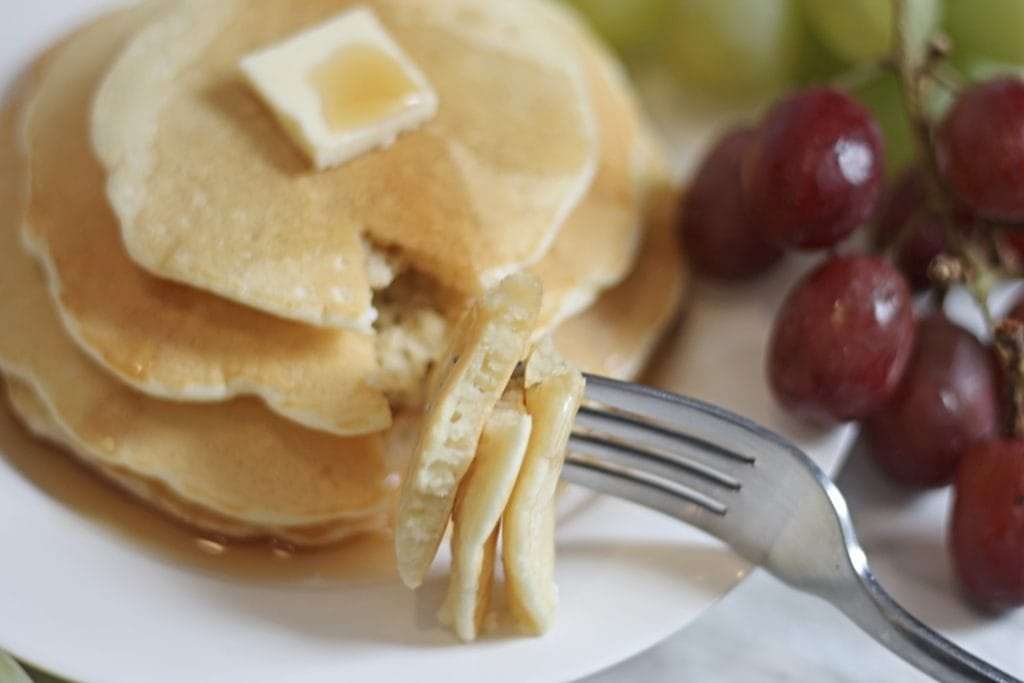 Forkful of pancakes with stack on plate