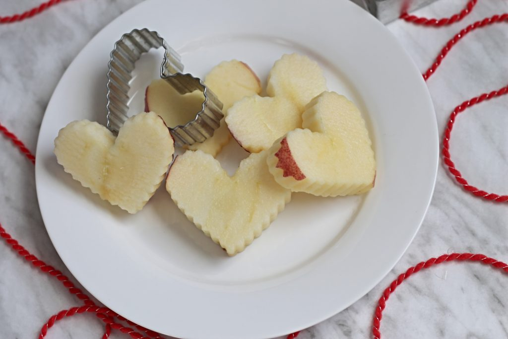 Heart shaped apple slices on white plate