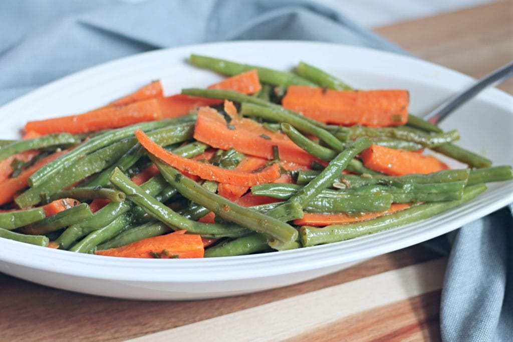 White serving dish filled with green beans and carrots on wooden cutting board