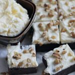 Banana Brownie Squares on parchment paper with bowl of frosting
