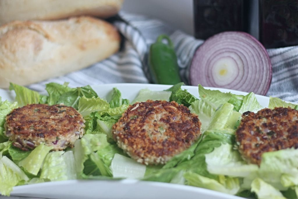 Tuna Cakes on top of a bed of lettuce on white platter