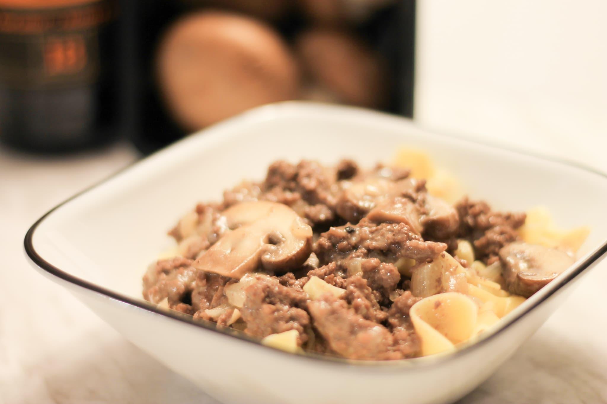 Ground Beef Stroganoff in white dish with cremini mushrooms blurred behind