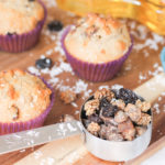 Mixed Berry Muffins with shredded coconut and dried fruit in measuring cup