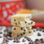 Stacked Chocolate Chip Citrus Shortbread Bars surrounded by scattered chocolate chips and Christmas tins