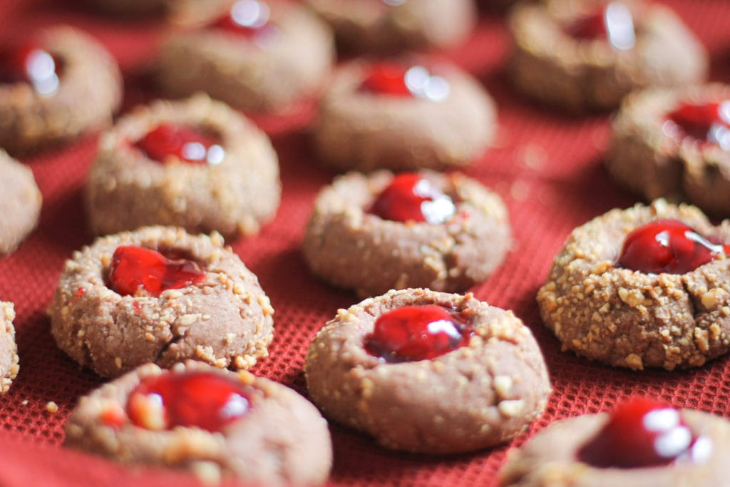Red tablecloth lined with freshly baked Thumbprint cookies