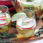 White Wine Sangria in stemless wine glasses with full pitcher behind - fresh fruit and rosemary on the cutting board