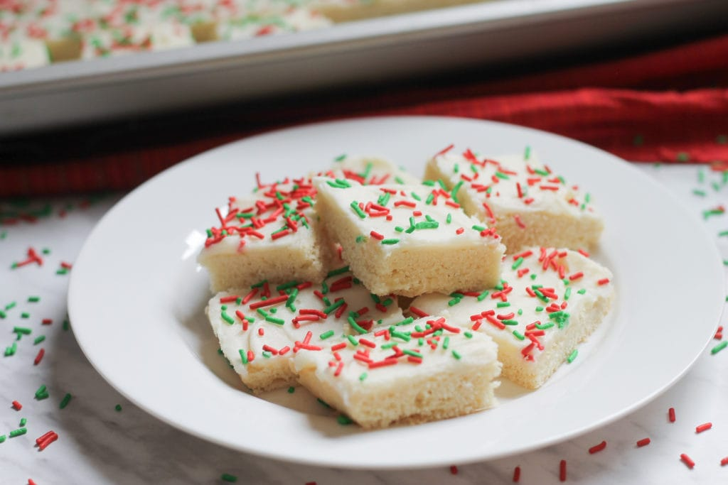 A white dessert plate piled high with frosted sugar cookie bars