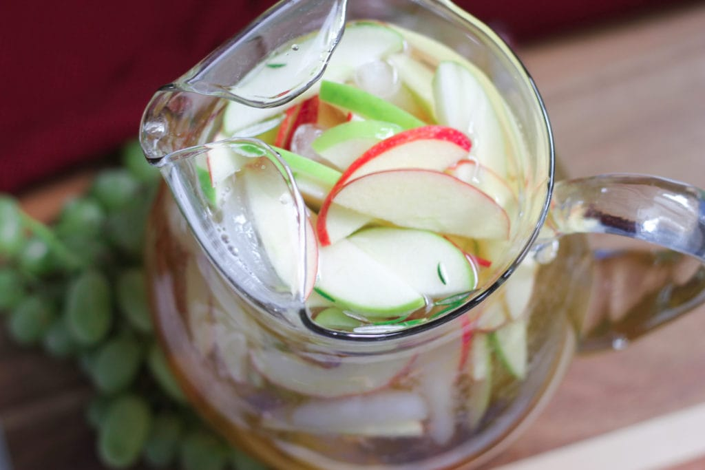 White sangria in clear glass pitcher with fresh cut apples and grapes