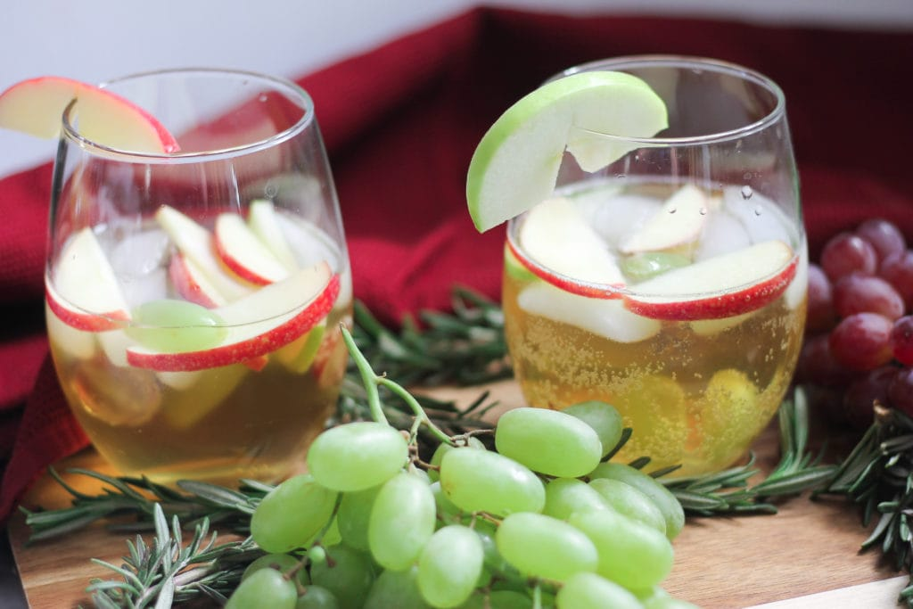 Two stemless wine glasses with white wine Christmas sangria and fresh grapes