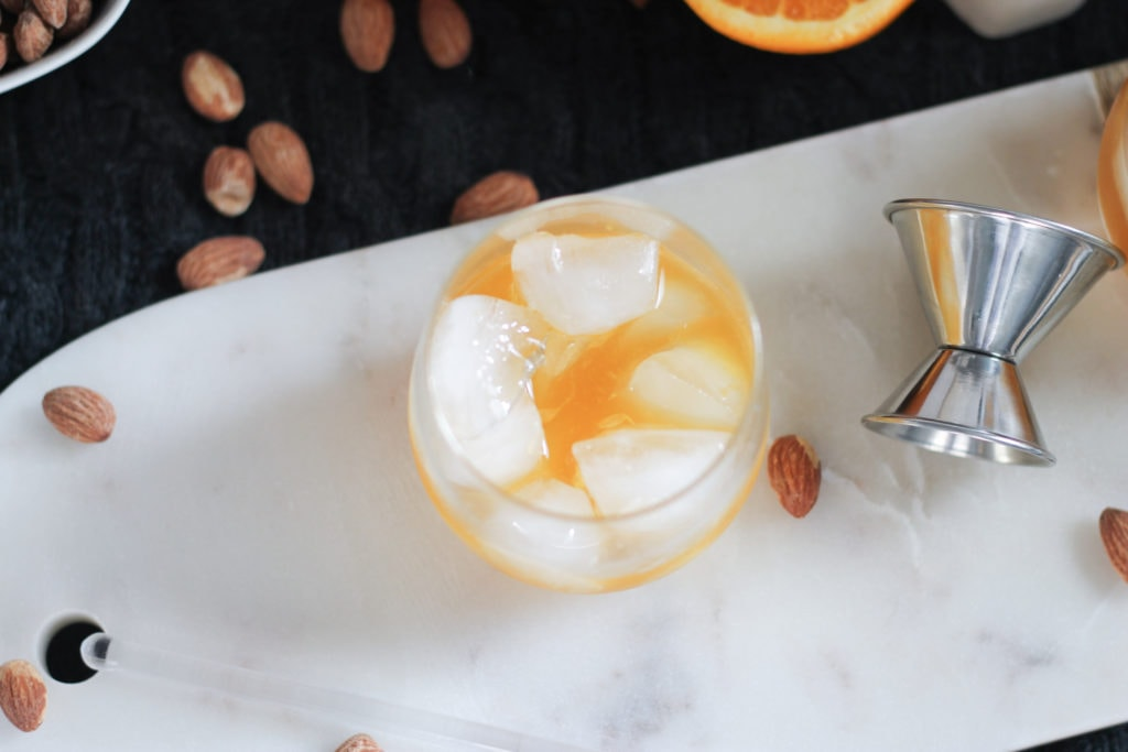 Marble cutting board with a clear glass of Bourbon Cocktail surrounded by almonds and citrus