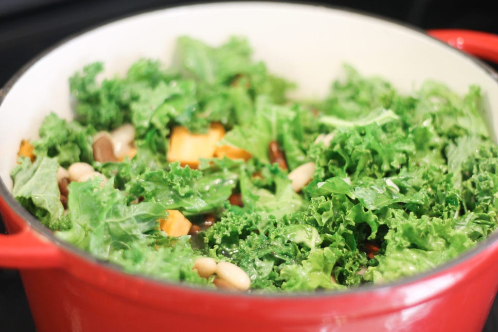 Kale and other vegetables with kidney beans simmering in a red dutch oven for soup.