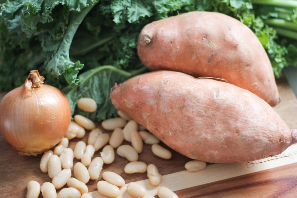 Fresh sweet potatoes, kale, onion and beans on wooden cutting board for making soup.