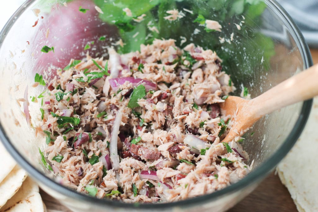Glass bowl of Mediterranean Tuna Salad with onions and parsley