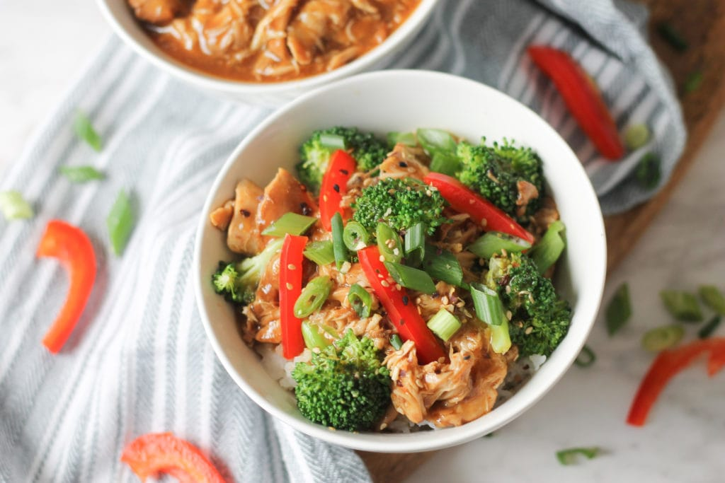 Bowl with garlic sesame chicken and steamed broccoli on table