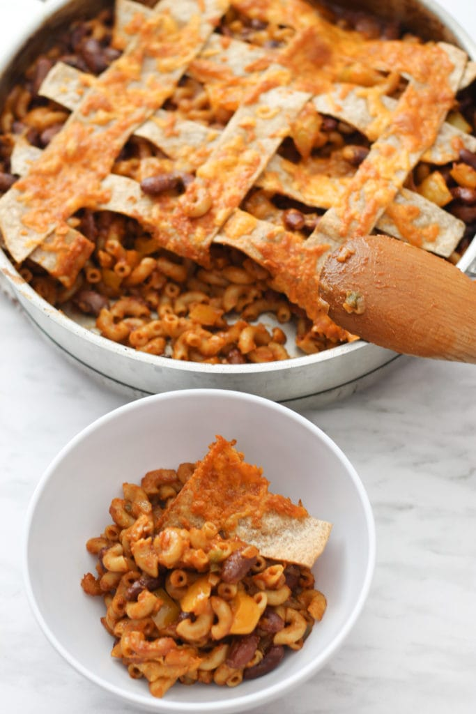 Skillet of Chili Mac with wooden spoon resting on the side and a white bowl with single serving.