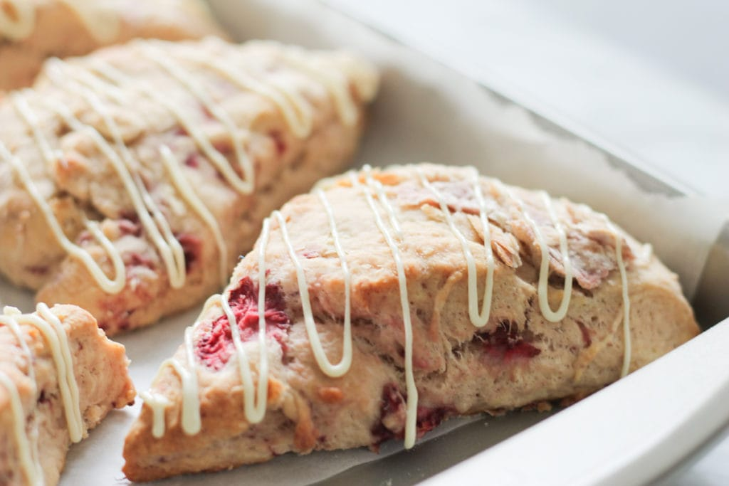 fresh baked strawberry scones with white chocolate drizzle on baking tray