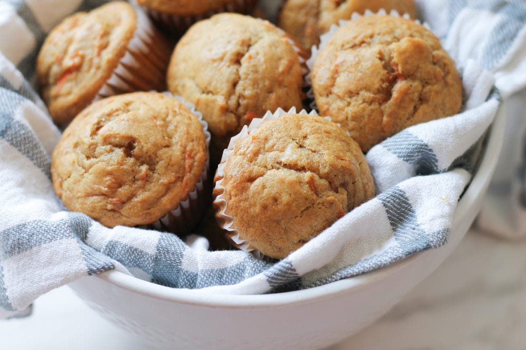 White ceramic bowl full of banana carrot muffins on top of a white and grey tea towel