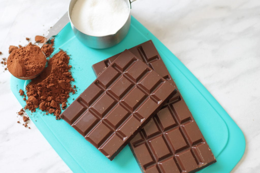 Teal cutting board with scoop of cocoa powder, measuring cup with sugar and two chunks of dark chocolate bar