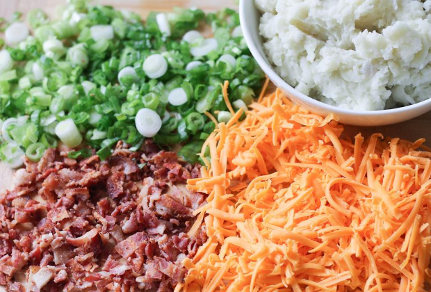 Cutting board with ingredients for casserole - grated cheese, mashed potatoes, crumbled bacon and sliced green onions
