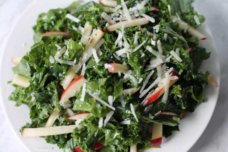 Fresh chopped kale with sliced apples and grated parmsean cheese mixed with dressing on a white plate